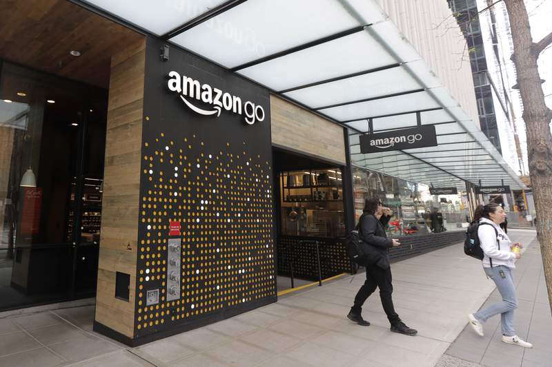 FILE - In this March 4, 2020 file photo, people walk out of an Amazon Go store, in Seattle.  Amazon said Wednesday, April 21, 2021 that it is rolling out its pay-by-palm technology to some of its Whole Foods supermarkets. The technology, called Amazon One, lets shoppers scan the palm of their hand and connect it to their credit card or Amazon accounts. (AP Photo/Ted S. Warren, File)