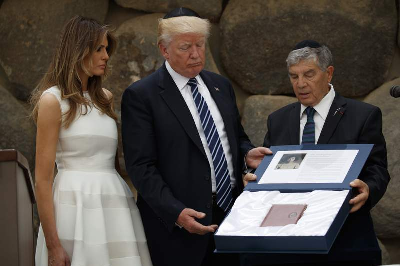 File - In this Tuesday, May 23, 2017 photo, first lady Melania Trump watch as Avner Shalev, chairman of the Yad Vashem Directorate, right, presents President Donald Trump a replica of a personal notebook of holocaust victim Ester Goldstein, in Jerusalem. Shalev, the chairman of Israel's Yad Vashem Holocaust Museum and Memorial said Sunday he will be stepping down from the role after 27 years. (AP Photo/Evan Vucci)