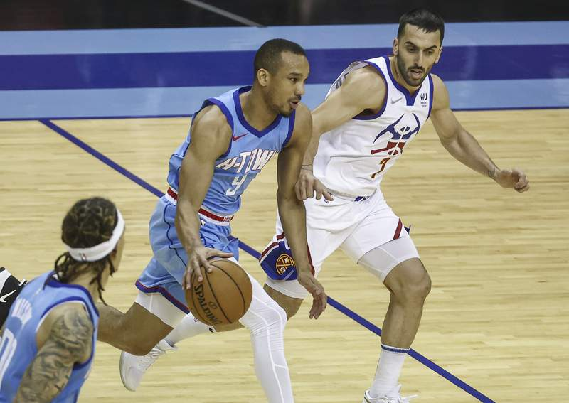 Houston Rockets guard Avery Bradley (9) dribbles the ball as Denver Nuggets guard Facundo Campazzo (7) defends during the second quarter of an NBA basketball game Friday, April 16, 2021, in Houston. (Troy Taormina/Pool Photo via AP)