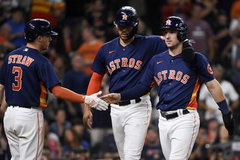 Houston Astros' Alex Bregman, right, celebrates scoring a run with Carlos Correa, center, and Myles Straw (3) during the eighth inning of a baseball game against the Texas Rangers, Sunday, May 16, 2021, in Houston. (AP Photo/Eric Christian Smith)