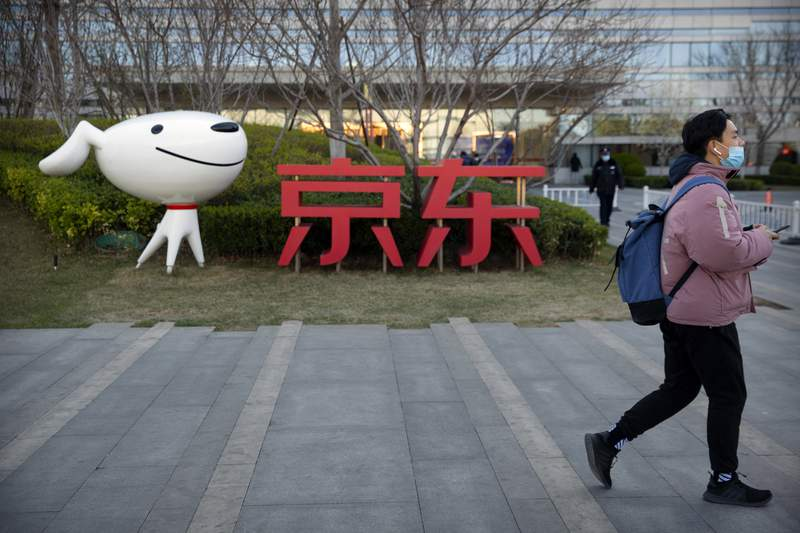 FILE - In this March 27, 2020, file photo, a man walks past the JD.com logo outside the company's headquarters in Beijing. Chinas market regulator on Thursday, Dec. 31, 2020, fined JD.com Inc., a unit of Alibaba Group and a third e-commerce outlet on charges of misreporting prices and other offenses amid a campaign to tighten official control over the booming industry. (AP Photo/Mark Schiefelbein, File)