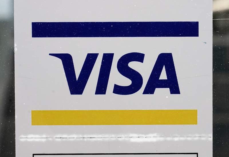 A Visa sign is displayed on the front door of a local business, Tuesday, April 27, 2021, in Urbandale, Iowa. Visa Inc.'s fiscal second-quarter profits fell 2% from a year earlier, as the company dealt with a slowdown across its payment network due to the global pandemic. The payment processing giant said Tuesday, April 27, 2021 that it earned $3.03 billion in its second quarter ended March 31, or $1.38 a share, down from $3.08 billion in the same period a year ago. Due to Visa buying back its own stock, the company's earnings per share last year was also $1.38. (AP Photo/Charlie Neibergall)