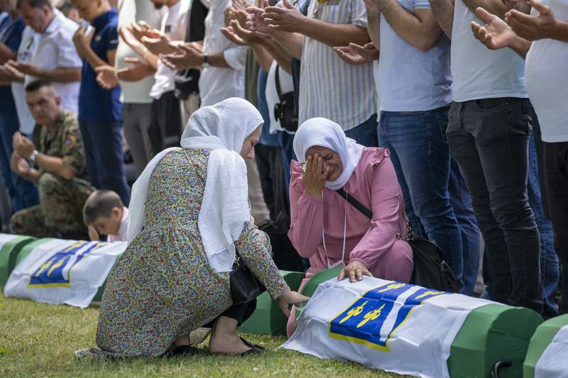 Women react as mourners prepare for the funeral of newly identified victims at the memorial cemetery in Potocari near Srebrenica, Bosnia, Sunday, July 11, 2021. Bosnia is marking the 26th anniversary of the Srebrenica massacre, the only episode of its 1992-95 fratricidal war that has been declared a genocide by international and national courts. The brutal execution of more than 8,000 Muslim Bosniaks by Bosnian Serb troops is being commemorated by a series of events Sunday. (AP Photo/Darko Bandic)