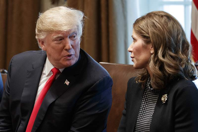 """FILE - In this Dec. 12, 2018 file photo, President Donald Trump speaks to then-Gov.-elect Kristi Noem, R-S.D., during a meeting at White House ,in Washington. From the earliest days of the pandemic, Trump called on governors to """"liberate"""" residents, reopen schools and get businesses back to normal.No governor followed that advice more closely  and with more attention-seeking fervor  than South Dakota Gov. Kristi Noem. (AP Photo/Evan Vucci File)"""