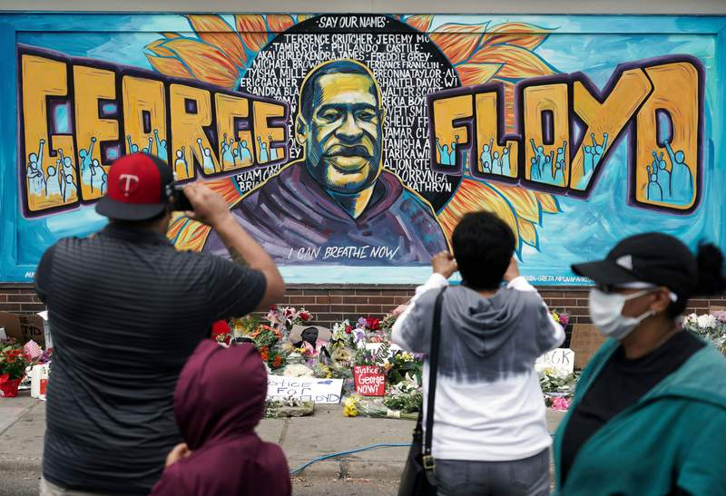 People gather at a memorial mural painted outside the Cup Foods store on Chicago Avenue in South Minneapolis where George Floyd died at the hands of police, Friday, May 29, 2020 in Minneapolis. (Brian Peterson/Star Tribune via AP)