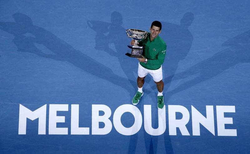 FILE - In this Monday, Feb. 3, 2020 file photo, Serbia's Novak Djokovic holds the Norman Brookes Challenge Cup after defeating Austria's Dominic Thiem in the men's singles final of the Australian Open tennis championship in Melbourne, Australia. The 2021 Australian Open will begin three weeks later than planned. That is part of a pandemic-altered 2021 tennis calendar released by the mens professional tour Wednesday, Dec. 16, 2020.  (AP Photo/Andy Wong, File)