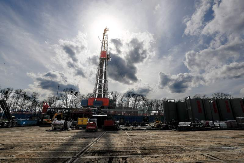 FILE - In this March 12, 2020, file photo, the sun shines through clouds above a shale gas drilling site in St. Mary's, Pa. President Donald Trump's administration is expected to undo Obama-era rules designed to limit greenhouse gas emissions from oil and gas fields and pipelines, formalizing the changes in the heart of the nation's most prolific natural gas reservoir and in the premier presidential battleground state of Pennsylvania. (AP Photo/Keith Srakocic, File)