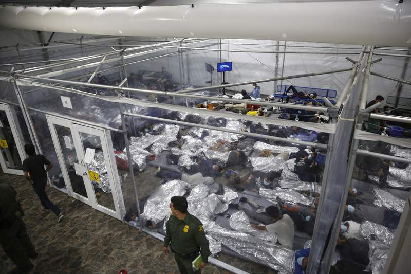 """FILE - In this March 30, 2021, file photo, minors lie inside a pod at the Donna Department of Homeland Security holding facility, in Donna, Texas. A move by Texas Gov. Greg Abbott to shutter dozens of shelters housing about 4,000 migrant children is threatening to disrupt a national program offering care for minors who cross the U.S.-Mexico border. The U.S. Department of Health and Human Services said Wednesday, June 2 2021, that it didn't intend to close any facilities but that it was """"assessing"""" the Republican governor's late Tuesday disaster declaration. (AP Photo/Dario Lopez-Mills, Pool, File)"""