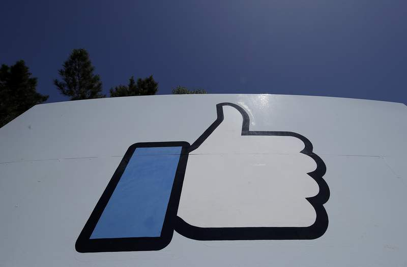 """FILE - This April 25, 2019, file photo shows the thumbs-up """"Like"""" logo on a sign at Facebook headquarters in Menlo Park, Calif. Facebook, following in Googles footsteps, says it plans to invest $1 billion to support the news industry over the next three years. The social networking giant, which has been tussling with Australia over a law that would make social platforms pay news organizations, said it has invested $600 million since 2018 for news. (AP Photo/Jeff Chiu, File)"""