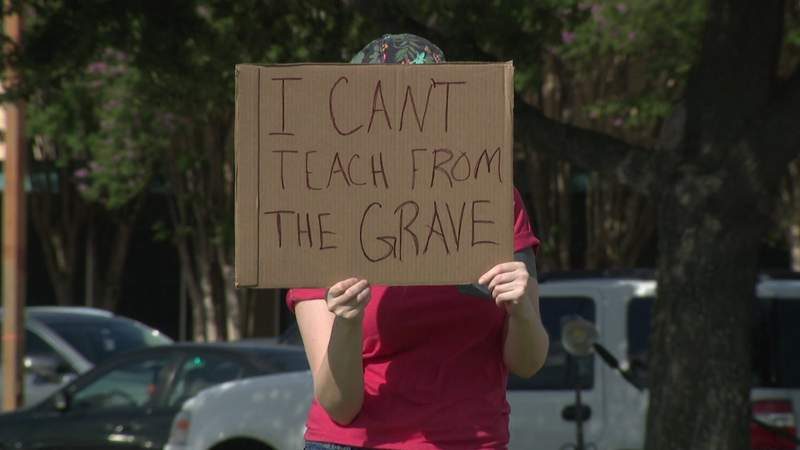 File: A teacher from the Cy-Fair Independent School District holds a sign in protest of in-person learning and going back to school in person.