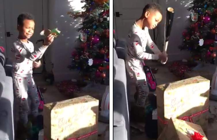 Logan Cumby opens his Christmas present to reveal a baseball bat.