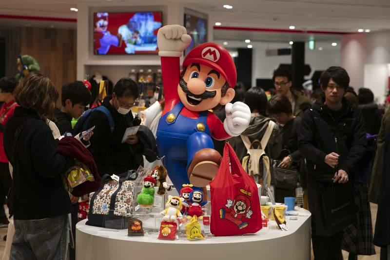 In this Jan. 23, 2020, photo, a Super Mario figure is on display as people shop at Nintendo's official store in the Shibuya district of Tokyo. Japanese video game maker Nintendo is reporting a 29% rise in quarterly profit on solid demand for its Switch console during the year-end shopping season. (AP Photo/Jae C. Hong)