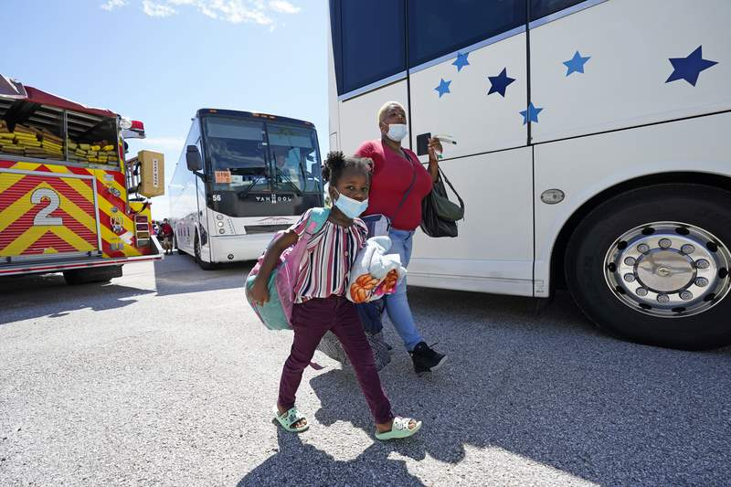 Alfreda Henderson, right, and her daughter, Miracle, 5, walk to board a bus as they evacuate Tuesday, Aug. 25, 2020, in Galveston, Texas. The evacuees from are being taken to Austin, Texas, as Hurricane Laura heads toward the Gulf Coast. (AP Photo/David J. Phillip)
