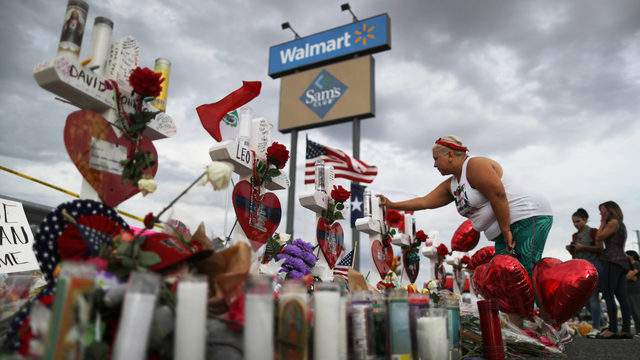 A woman touches a cross at a makeshift memorial for victims outside Walmart, near the scene of a mass shooting on Aug. 3 which left at least 22 people dead, on Aug. 6, 2019, in El Paso, Texas.