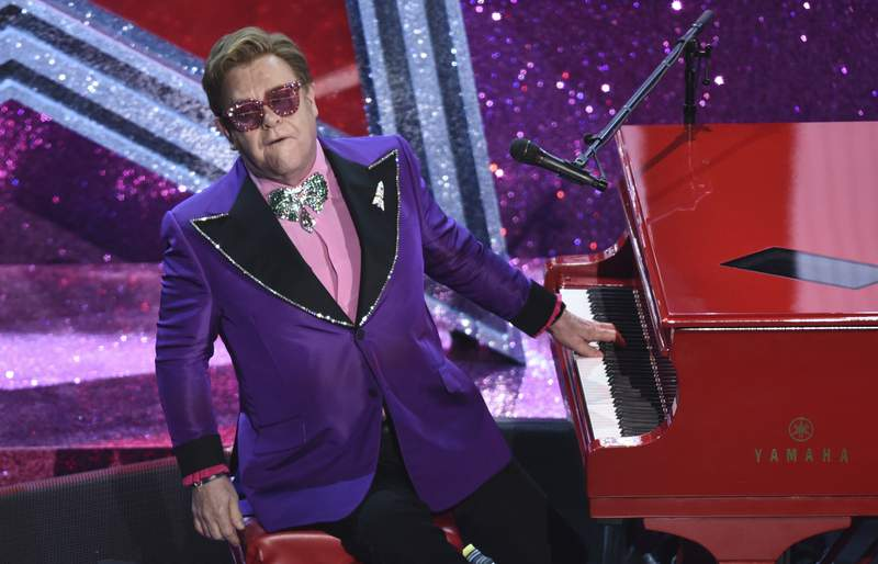 """FILE - In this Sunday, Feb. 9, 2020 file photo, Elton John performs """"(I'm Gonna) Love Me Again"""" nominated for the award for best original song from """"Rocketman"""" at the Oscars, at the Dolby Theatre in Los Angeles. Dozens of U.K. music stars including Elton John, Ed Sheeran and conductor Simon Rattle on Wednesday Jan. 20, 2021, say musicians have been shamefully failed by the British government, which has left them facing post-Brexit restrictions on touring in the European Union. (AP Photo/Chris Pizzello, File)"""