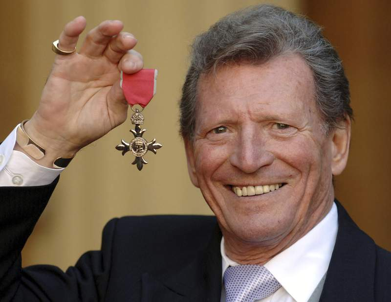 FILE - In this March 7, 2007 file photo, actor Johnny Briggs poses for the media after collecting an MBE from Queen Elizabeth II at Buckingham Palace in London. British actor Johnny Briggs, best known for his role as businessman Mike Baldwin in the long-running TV soap opera Coronation Street, has died. He was 85. A statement from his family released Sunday, Feb. 28, 2021 said Briggs died peacefully after a long illness. (Fiona Hanson/PA via AP, file)