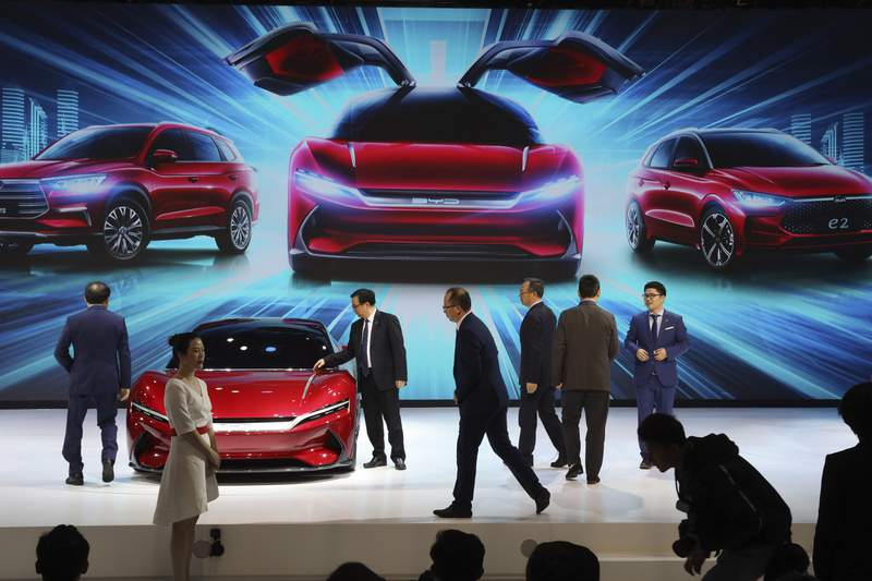 FILE - In this April 16, 2019, file photo, attendees take a close look at cars from BYD at the Auto Shanghai 2019 show in Shanghai. Chinas auto sales plunged 81.7% in February, 2020,  from a year ago after Beijing shut down much of the economy to fight a virus outbreak, adding to problems for an industry that already was struggling with shrinking demand. (AP Photo/Ng Han Guan, File)