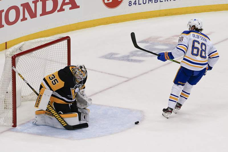 The puck bounces out of the net after Buffalo Sabres' Victor Olofsson (68) scored on a penalty shot on Pittsburgh Penguins goaltender Tristan Jarry (35) during the third period of an NHL hockey game, Wednesday, March 24, 2021, in Pittsburgh. Olofsson was awarded a penalty shot on the play and scored on that. The Penguins won 5-2. (AP Photo/Keith Srakocic)