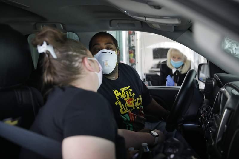 """FILE PHOTO - Kerri Sims, left, and Christopher McCall of Las Vegas lean in to kiss each other while wearing masks at their drive-thru wedding at A Little White Wedding Chapel, Friday, May 15, 2020, in Las Vegas. """"This is definitely not how we planned to get married, but what can you do?"""" said Sims. (AP Photo/John Locher)"""