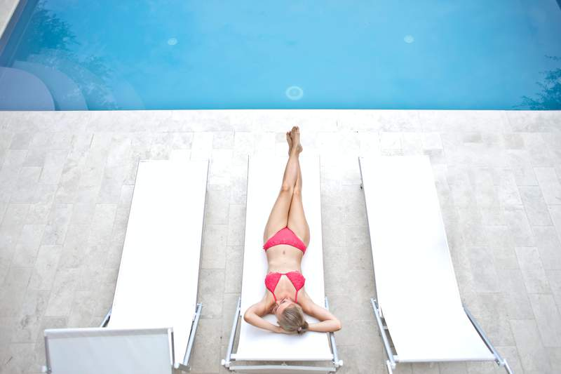 A woman lounges at the pool.
