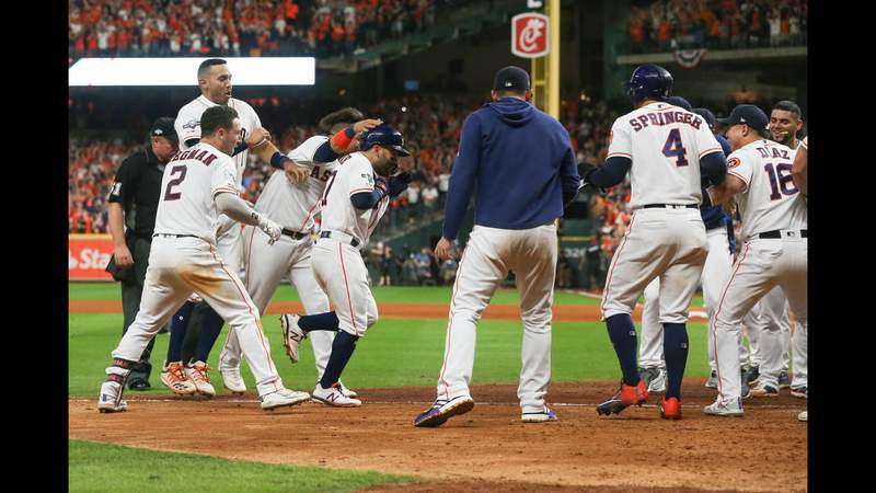 HOUSTON, TEXAS - OCTOBER 19:  Jose Altuve #27 of the Houston Astros comes home to score after his walk-off two-run home run to win game six of the American League Championship Series 6-4 against the New York Yankees at Minute Maid Park on October 19, 2019 in Houston, Texas. (Photo by Bob Levey/Getty Images)