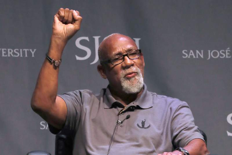 FILE - In this Oct. 17, 2018, file photo, 1968 Olympic athlete John Carlos raises his fist as he speaks about his experience as Olympians who participated in Mexico City in 1968 during the 50th Anniversary of the Defining Moment in Sports Social Activism Historic Town Hall at San Jose State University in San Jose, Calif. Olympic protestor John Carlos co-authored a letter with an influential American athletes' group calling on the IOC to abolish the rule that bans protests at the Olympics and replace it with a policy written in collaboration with athletes. Carlos and Tommie Smith raised their fists on the medals stand at the 1968 Olympics to protest racial inequality in the United States.  (AP Photo/Tony Avelar, File)