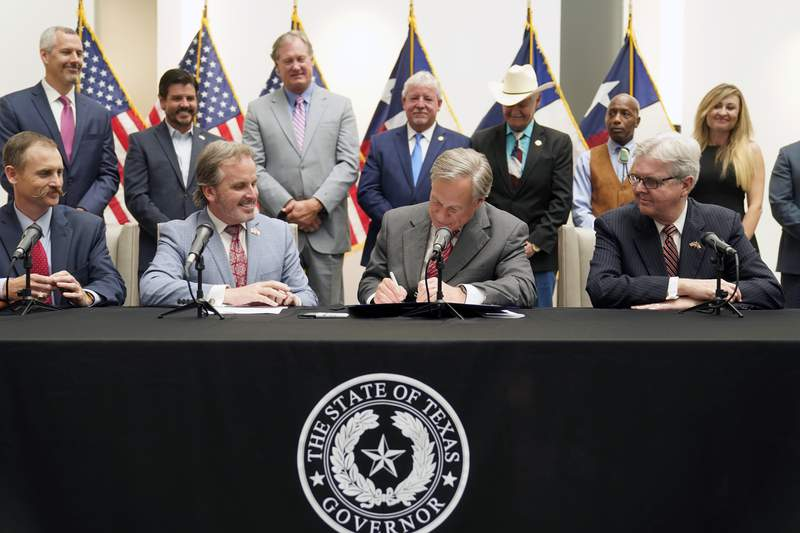 Texas Gov Greg Abbott signs Senate Bill 1, also known as the election integrity bill, into law with State Sen. Bryan Hughes, R-Mineola, front center left, Andrew Murr, R-Junction, front left, and Lieutenant Governor Dan Patrick, front right looking on with others in the back ground in Tyler, Texas, Tuesday, Sept. 7, 2021. (AP Photo/LM Otero)