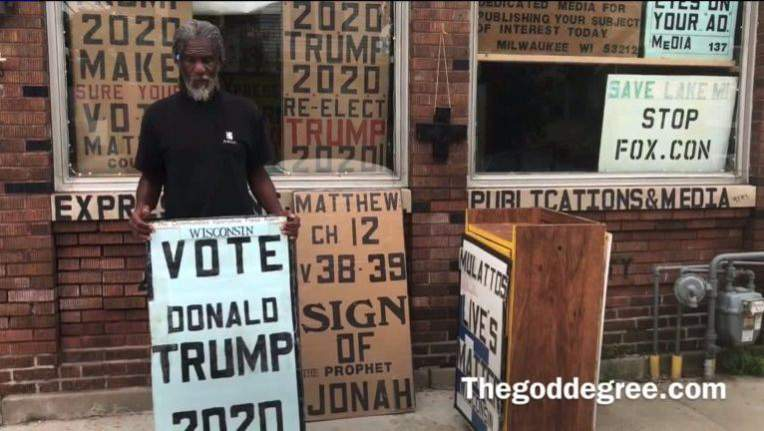 """Bernell Tremmel, 60, is shown here carrying """"Vote Trump"""" and bible verse signs at a street corner in Milwaukee."""