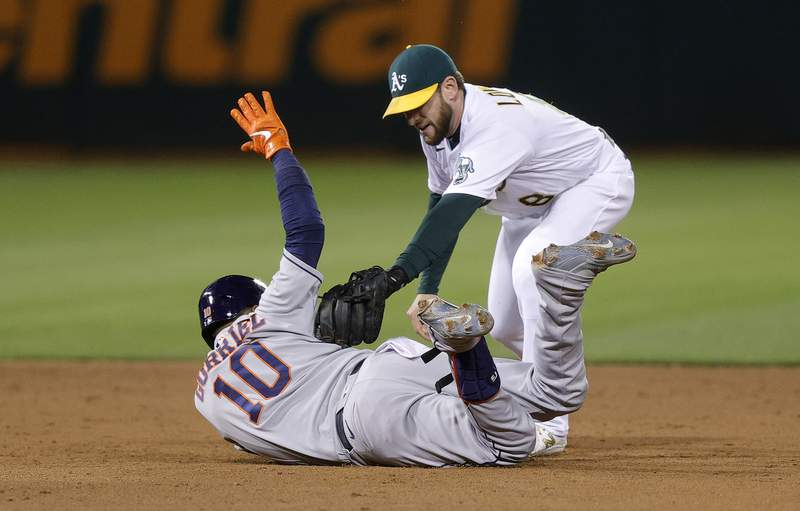OAKLAND, CALIFORNIA - MAY 19:  Yuli Gurriel #10 of the Houston Astros slides under the tag of Jed Lowrie #8 of the Oakland Athletics for a double in the eighth inning that scored two runs at RingCentral Coliseum on May 19, 2021 in Oakland, California. (Photo by Ezra Shaw/Getty Images)