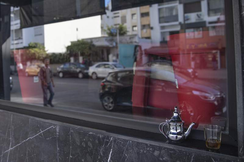 FILE - In this Monday, March 16, 2020 file photo, a glass of Moroccan tea is left by a window of a closed down coffee shop, after the Moroccan government announced further restrictions to avoid the spread of coronavirus, including closure of cafes and mosques, in the capital Rabat, Morocco. Morocco has imposed a curfew, closed restaurants in major cities and banned public and private gatherings for three weeks  including the usually festive New Year's Eve  to curb the spread of the virus.The curfew between 9 p.m and 6 a.m went into effect Wednesday, Dec. 23, 2020 and is set to last until Jan. 13.  (AP Photo/Mosa'ab Elshamy, File)