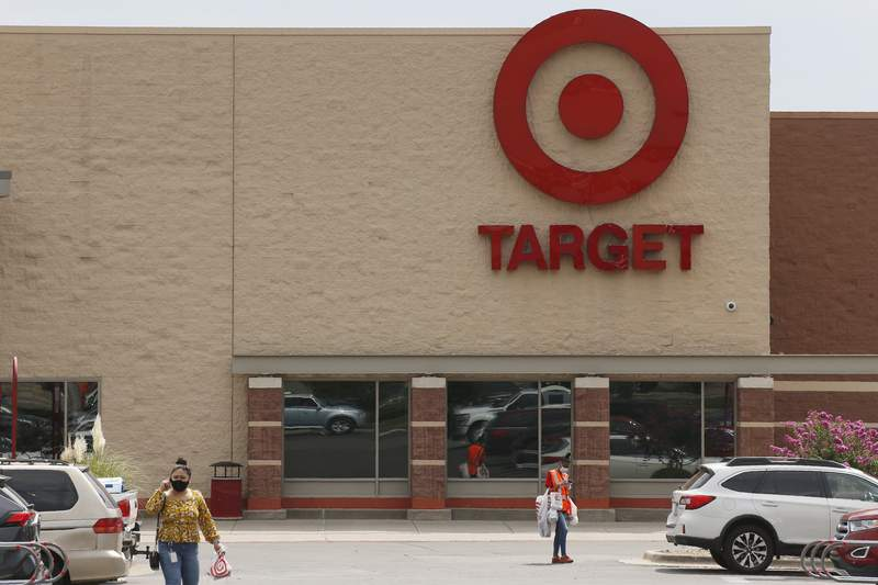 FILE - In this Tuesday, Aug. 4, 2020 file photo, people walk through the parking lot at a Target store in Oklahoma City. Target has reported that its sales as measured by a key metric registered their strongest performance to date for the companys fiscal second quarter. It's the latest evidence that big-box stores are becoming consumers' prime shopping destinations during the pandemic.  (AP Photo/Sue Ogrocki, File)