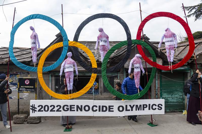 FILE - In this Feb. 3, 2021, file photo, exile Tibetans use the Olympic Rings as a prop as they hold a street protest against the holding of 2022 Winter Olympics in Beijing in Dharmsala, India. Some of the worlds largest broadcasters including American network NBC are being asked to cancel plans to cover the 2022 Winter Olympics in Beijing over alleged human rights abuses in the country. The Games open on Feb. 4. (AP Photo/Ashwini Bhatia, File)