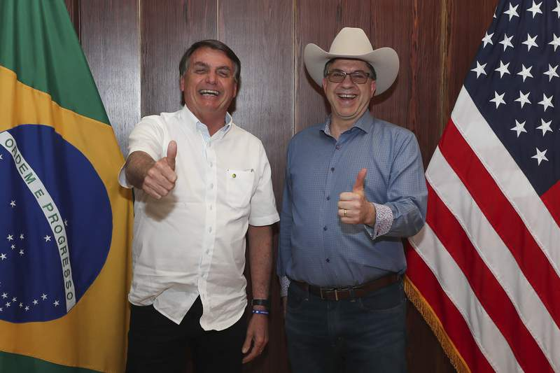 In this photo distributed by Brazil's presidential press office, Brazilian President Jair Bolsonaro, left, and U.S. Ambassador Todd Chapman pose for a photo during an event to mark U.S. Independence Day at the ambassador's residence in Brasilia, Brazil, Saturday, July 4, 2020. (Isac Nobrega/Brazil's presidential press office via AP)