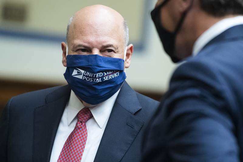 Postmaster General Louis DeJoy, left, talks with Rep. Mark Walker, R-N.C., before a House Oversight and Reform Committee hearing on the Postal Service on Capitol Hill, Monday, Aug. 24, 2020, in Washington. (Tom Williams/Pool via AP)