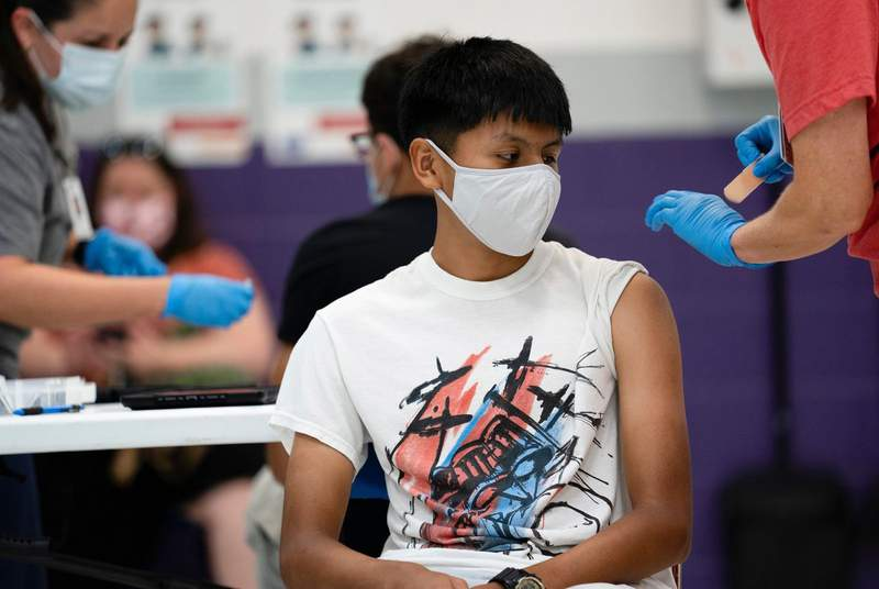 Anthony Pea, 15, sits after receiving a dose of the Pfizer vaccine at a clinic organized by the Travis County Mobile Vaccine Collaborative at Rodriguez Elementary School on July 28, 2021.