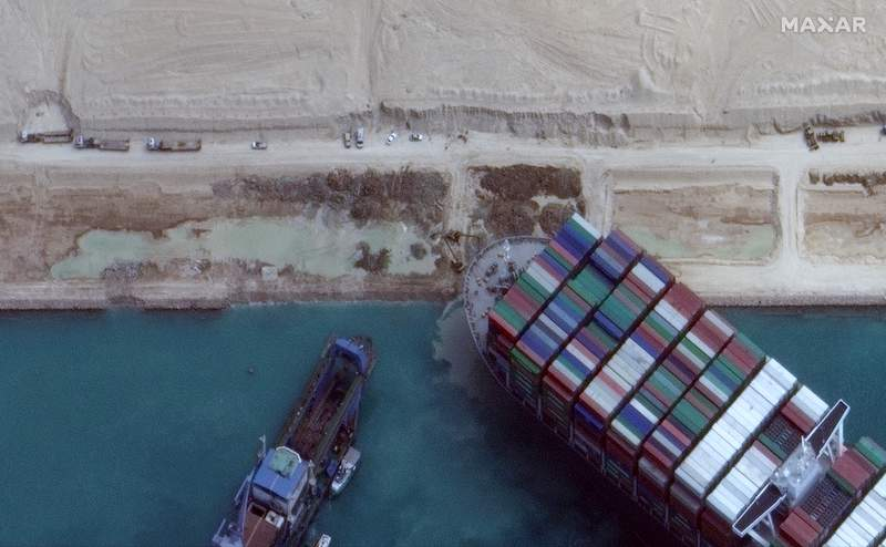This satellite image from Maxar Technologies shows excavation work in an atempt to free the cargo ship MV Ever Given that is stuck in the Suez Canal near Suez, Egypt, Sunday, March 28, 2021. Two additional tugboats sped Sunday to Egypt's Suez Canal to aid efforts to free the skyscraper-sized container ship wedged for days across the crucial waterway, even as major shippers increasingly divert their boats out of fear the vessel may take even longer to free. (Maxar Technologies via AP)