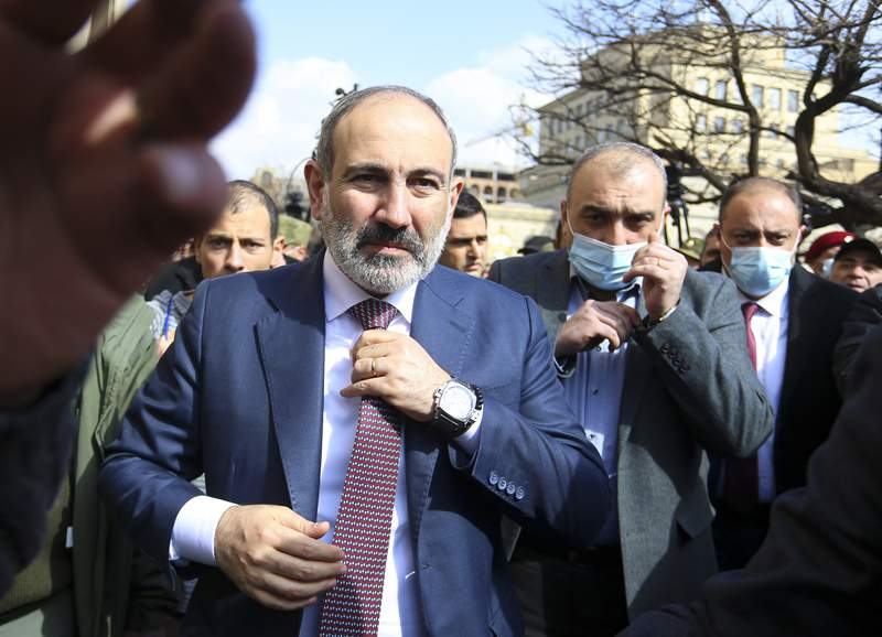 FILE - In this Thursday, Feb. 25, 2021 file photo, Armenian Prime Minister Nikol Pashinyan arrives at the main square in Yerevan, Armenia. Armenia's embattled prime minister has confirmed that he will step down from the post in April in order to allow early parliamentary elections. Nikol Pashinyan has faced weeks of protests calling for his ouster in the wake of Armenia's defeat in last year's war with Azerbaijan over the Nagorno-Karabakh region. In a move to defuse the political crisis, Pashinyan two weeks ago announced early elections would be held on June 20.  I will resign in April  not to leave power, but to hold early parliamentary elections, I will continue to act as prime minister as head of the Cabinet, Pashinyan said in a meeting with residents of the village of Aragats on Sunday, March 28, 2021 . He did not give a specific date for stepping down. (Stepan Poghosyan/PHOTOLURE via AP, File)