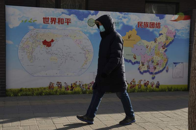 """A man walks past a poster with the slogans """"World Peace"""" and """"Ethnic Unity"""" in Beijing, China Monday, Jan. 11, 2021. A Chinese official on Monday denied Beijing has imposed coercive birth control measures among Muslim minority women, following an outcry over a tweet by the Chinese Embassy in Washington claiming that government polices had freed women of the Uighur ethnic group from being """"baby-making machines."""" (AP Photo/Ng Han Guan)"""