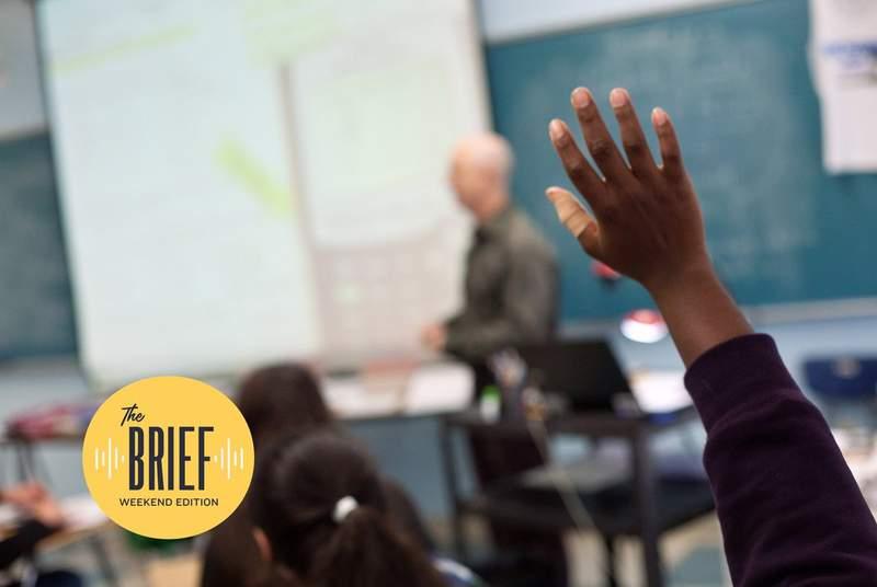 A student raises his hand in class at James Bowie High School in Austin.