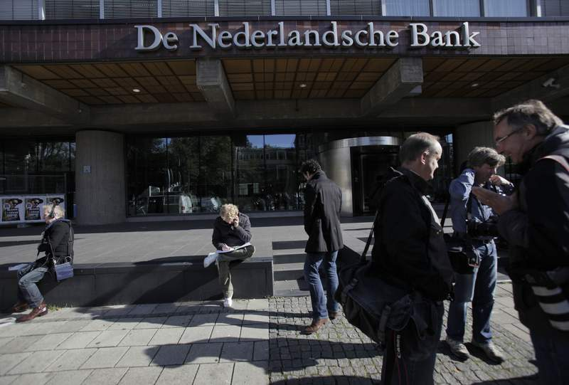 FILE - IN this Monday, Oct. 12, 2009 file photo, reporters wait outside the De Nederlandsche Bank, the Dutch national bank, in Amsterdam, Netherlands. The Netherlands central bank has moved its Dutch-based stock of gold from its headquarters in Amsterdam to a safe in the nearby city of Haarlem. The 14,000 bars and about 1,000 boxes of gold coins worth a total of some 10 billion euros ($11.7 billion) were transported in a meticulously and closely guarded operation that ended Saturday, Oct. 3, 2020. (AP Photo/Peter Dejong, File)