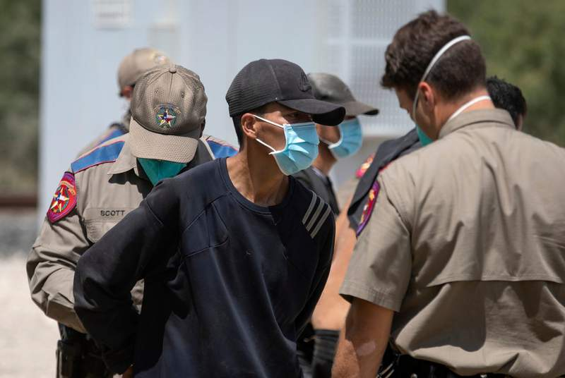 A migrant is readied to board a law enforcement van after being apprehended by Department of Public Safety officers at a train depot in Spofford on Aug. 25, 2021.