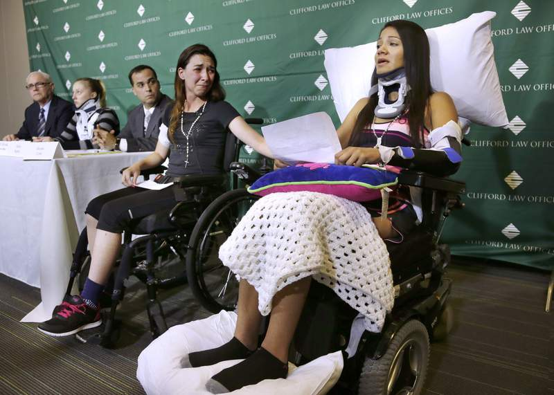 FILE - In this June 17, 2014, file photo, Circus acrobat Julissa Segrera, second from right, of the United States, and Dayana Costa, right, of Brazil, are tearful as Costa reads a statement at Spaulding Rehabilitation Hospital in Boston. They were among the eight acrobats injured when the apparatus from which they were suspended fell, sending them plummeting to the ground during a May 4 performance of the Ringling Bros. and Barnum & Bailey Circus in Providence, R.I. Their lawyer confirmed Monday, Dec. 21, 2020, they had reached a $52.5 million settlement with the ownership and management of the arena where the circus was held for injuries they sustained. (AP Photo/Steven Senne, File)