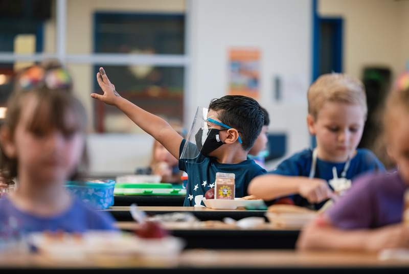 A student wearing a mask and face shield eats lunch at Blanco Vista Elementary School in San Marcos on Aug. 23, 2021.