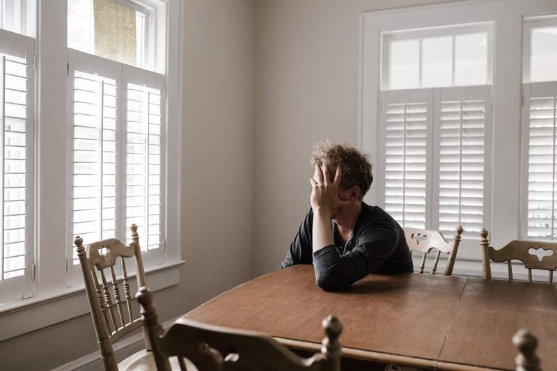 I man sits at a table, staring out the window.