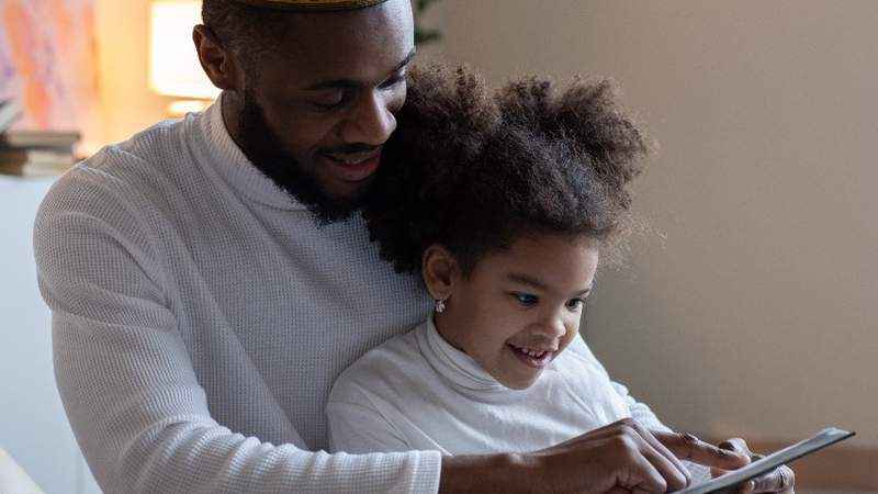 A man reads to a young girl.