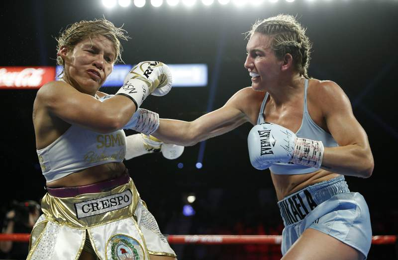 FILE - In this June 15, 2019, file photo, Mikaela Mayer, right, lands a right to Lizbeth Crespo in a boxing match in Las Vegas. Junior lightweight contender Mayer has tested positive for COVID-19 and has been pulled from the co-main event of Las Vegas first major boxing card since the start of the coronavirus pandemic. (AP Photo/John Locher, File)