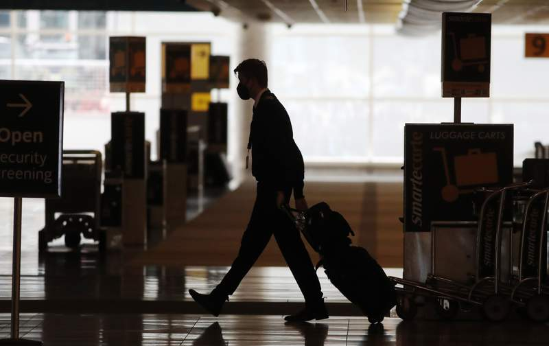 FILE - In this Thursday, April 9, 2020, file photo, a lone airline crew member pulls his bags behind him as he walks through the baggage-claim area at Denver International Airport in Denver, amid the coronavirus outbreak. (AP Photo/David Zalubowski, File)