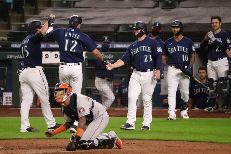 Evan White #12 of the Seattle Mariners celebrates his three-run home run against the Houston Astros with Kyle Seager and Ty France #23 in the seventh inning at T-Mobile Park on September 21, 2020 in Seattle, Washington. (Photo by Abbie Parr/Getty Images)