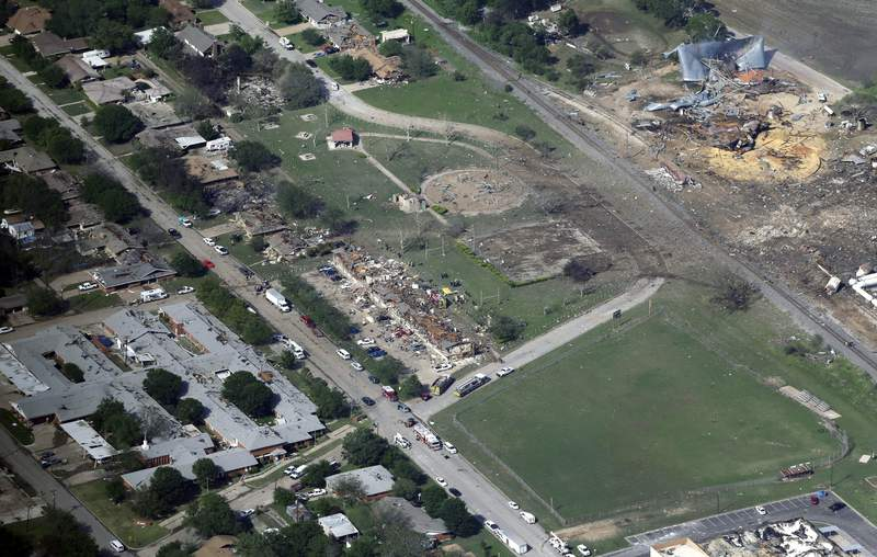 """FILE - This April 18, 2013 aerial file photo, shows the remains of a nursing home, left, apartment complex, center, and fertilizer plant, right, destroyed by an explosion at a fertilizer plant in West, Texas. Images of a massive explosion in the Lebanese capital looked depressingly familiar to West, Texas Mayor Tommy, whose small town in 2013 was partly leveled by one of the deadliest fertilizer plant explosions in U.S. history. """"I don't know what people were thinking about storing that stuff,"""" Muska said, Wednesday, Aug. 5, 2020. (AP Photo/Tony Gutierrez, File)"""