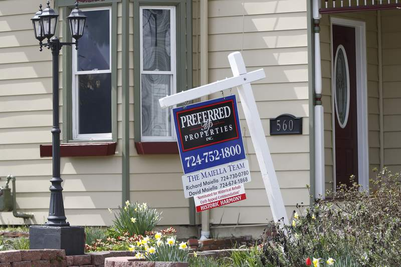 This April 16, 2020 photo shows a real estate company sign that marks a home for sale in Harmony, Pa.  U.S. new home sales plunged 15.4% in March as the lockdowns that began in the middle of the month began to rattle the housing market.  The Commerce Department reported Thursday, April 23,  that sales of new single-family homes dropped to a seasonally ajdjusted annual rate of 627,000 last month after sales had fallen 4.6% in February.  (AP Photo/Keith Srakocic)